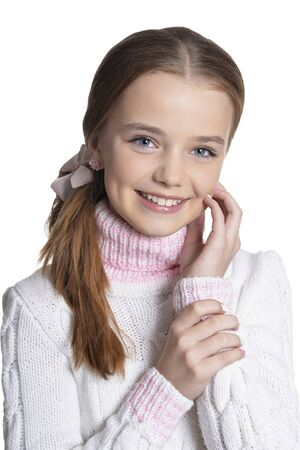 Portrait of smiling little girl wearing warm sweater on white background