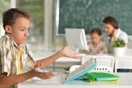 Boy doing homework and teacher with girl using computer on background Stock Photo