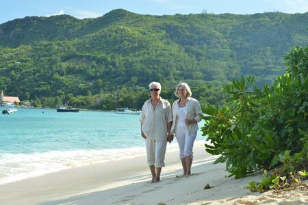 Portrait of happy elderly couple resting on beach. Travel