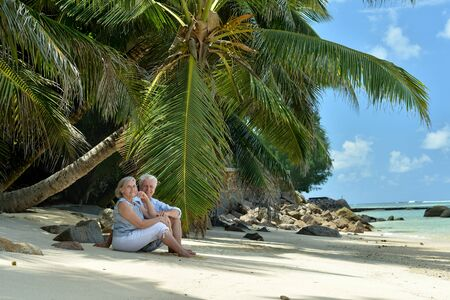 Portrait of elderly couple resting on beach. Travel Stock Photo