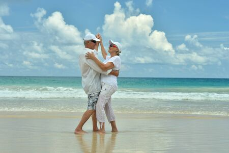 Portrait of happy elderly couple resting on beach dancing