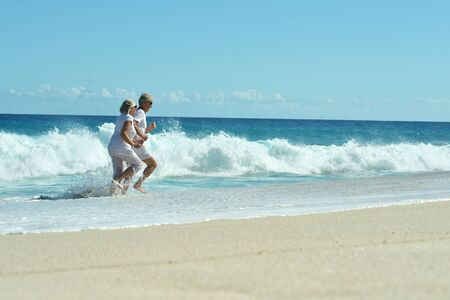 Portrait of happy elderly couple running on tropical beach