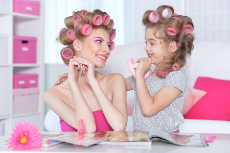 portrait of happy Mother and little daughter with hair curlers
