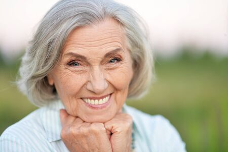 Portrait of happy senior beautiful woman posing in spring park Stock Photo