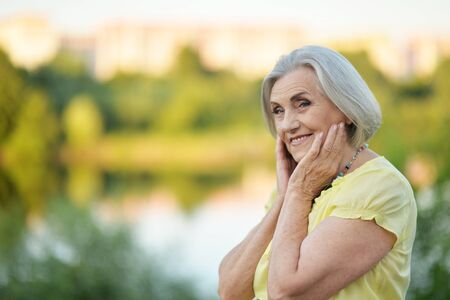 Portrait of happy senior beautiful woman by lake Stock Photo