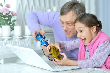 Father with little daughter playing computer game 스톡 콘텐츠