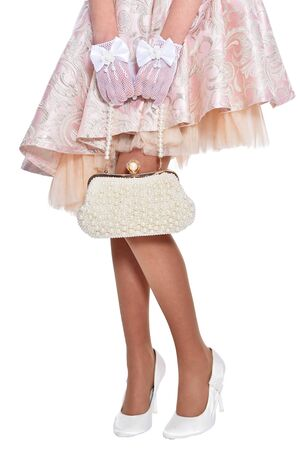 Cropped shot of little girl posing with purse on white background
