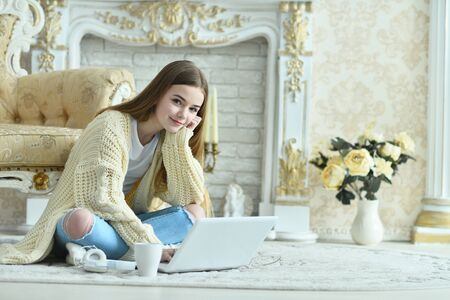 Portrait of beautiful teen girl sitting on floor near vintage armchair 版權商用圖片