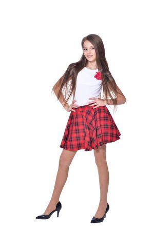Bambina felice che indossa tacchi alti in posa su sfondo bianco
