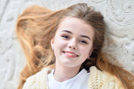Portret van een mooi tienermeisje dat op de vloer in de kamer ligt Stockfoto