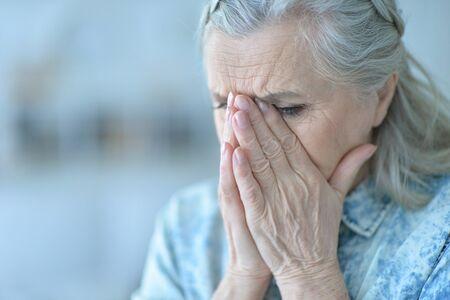 Close up portrait of beautiful sad senior woman posing at home