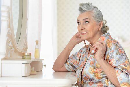 Portrait of happy senior woman applying makeup Stock Photo