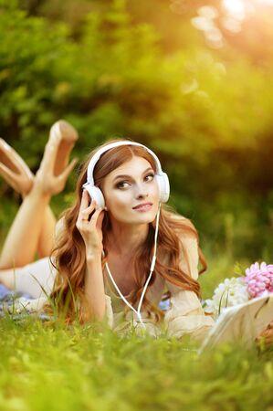Portret pięknej młodej kobiety leżącej na zielonej łące