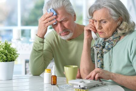 Portrait of ill senior couple with pills at home Stock Photo