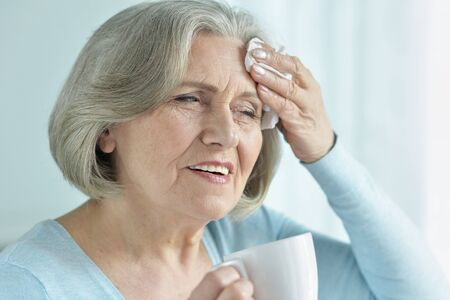 Portrait of senior woman with headache holding hand on head