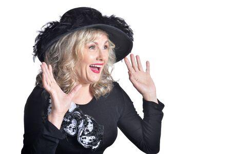 Emotional senior woman wearing black hat posing on white background