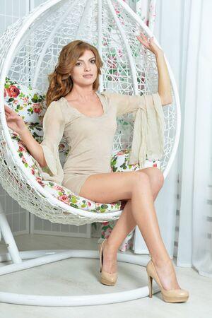 Hermosa mujer joven sentada en una silla colgante