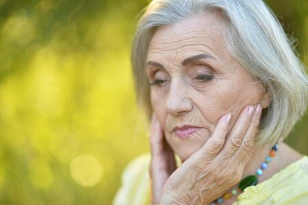 Portrait of sad senior beautiful woman posing in spring park Standard-Bild