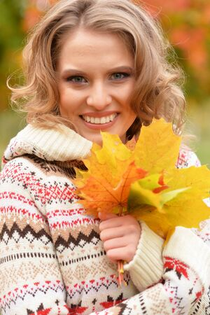 Portrait of beautiful young woman holding autumn leaves