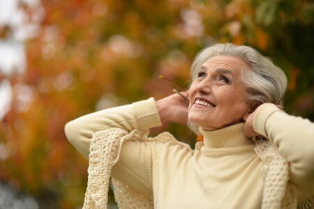 Portrait of happy senior woman smiling and posing in autumn park Banco de Imagens
