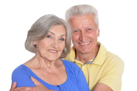 happy beautiful senior couple huging and posing on white background
