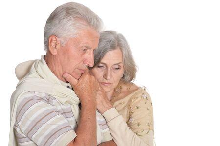 Portrait of sad senior couple posing on white background