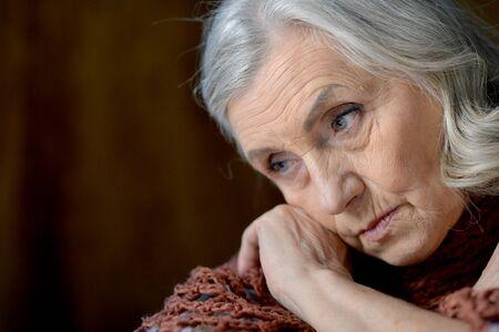 Close up portrait of cute sad senior woman