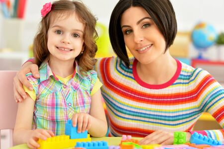 Close up portrait of cute little girl and her mother playing colorful plastic blocks together in her room