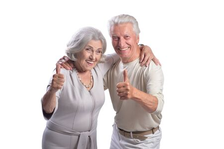 Happy senior couple with thumbs up on white background