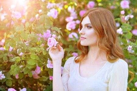 Beautiful young woman posing by rose bush in summer park