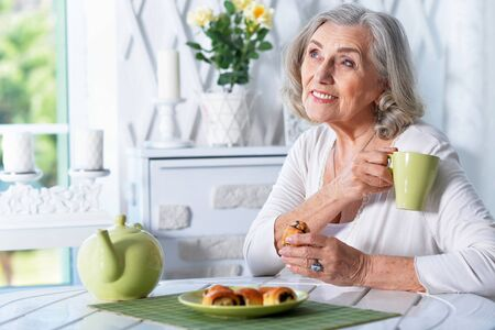 Portrait of beautiful smiling senior woman drinking tea while sitting at kitchen table