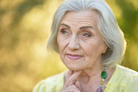 Porträt der traurigen älteren schönen Frau im Frühlingspark