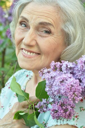 Porträt der glücklichen älteren schönen Frau mit Flieder