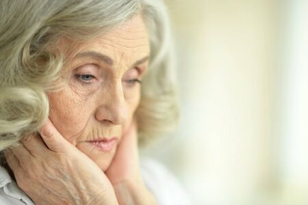 Portrait of beautiful sad senior woman posing at home Banco de Imagens