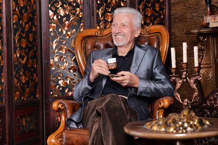 Portrait of smiling senior man drinking coffee at home Zdjęcie Seryjne