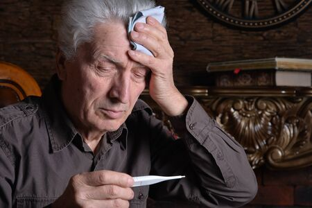 Portrait of sick senior man with thermometer