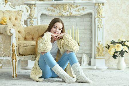 Portret van een mooi tienermeisje dat op de vloer zit