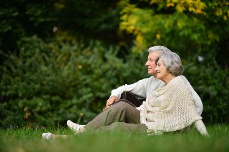 Portrait of elderly couple sitting on green grass in the summer park