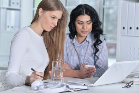 Portrait of two young women working at office with laptop