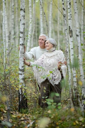 Portrait of happy senior couple resting in autumn birch forest