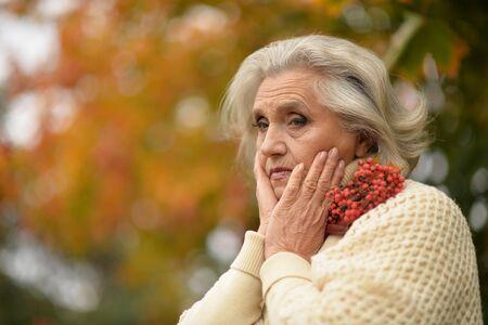 Portrait of sad senior woman in autumn park