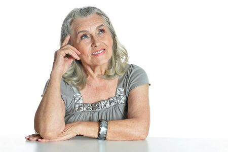 Emotional senior woman at table on white background