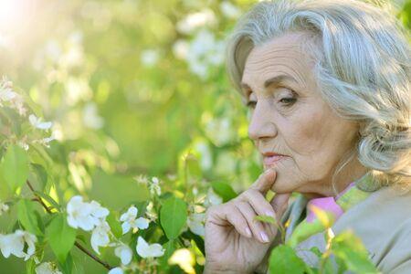 Close up portrait of cute senior woman praying outdoors 스톡 콘텐츠