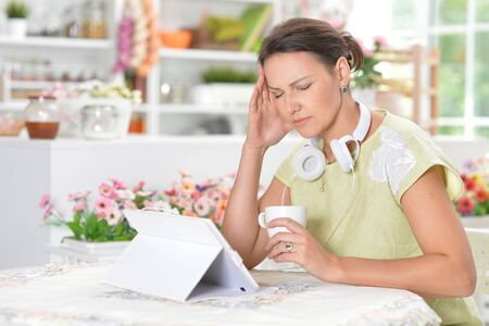 Young woman with headache using digital tablet Banco de Imagens