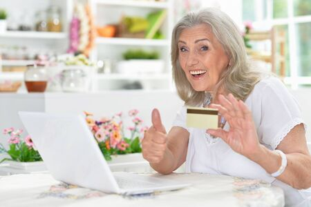 Happy senior woman holding credit card and showing thumb up