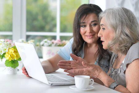Portrait of two mature women using laptop