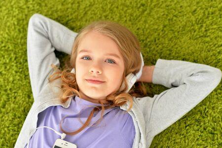 Portret van een mooi tienermeisje dat op de vloer ligt Stockfoto
