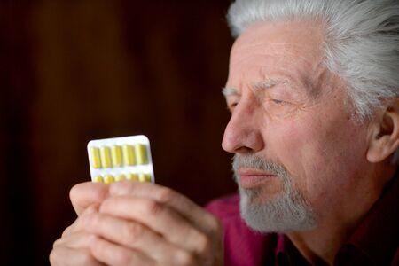 Portrait of sad sick senior man with pills