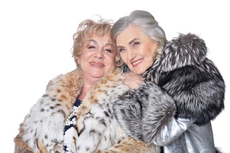 Portrait of senior women in fur coats isolated on white background