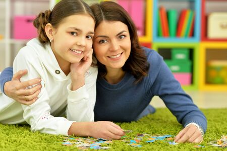 Portrait of mother with little daughter collecting puzzles Banco de Imagens - 128858754